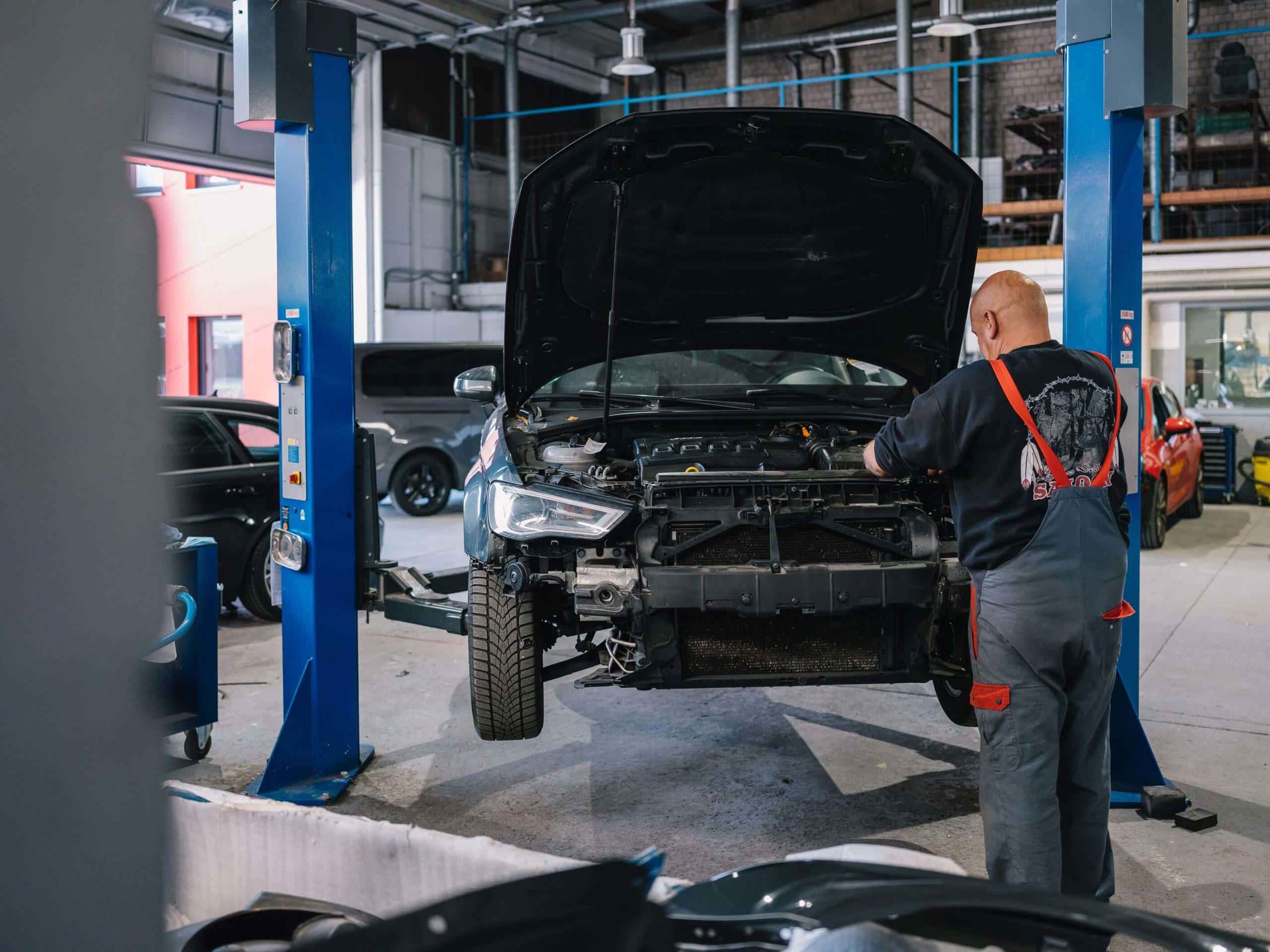Werkstattmitarbeiter inspiziert ein hochgebocktes Auto in der Motorhaube